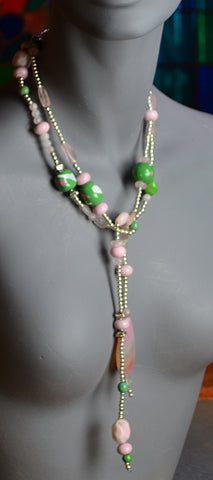 The warm, soothing pink of opal and pink glass is in contrast to the cool green and white ceramic squares
