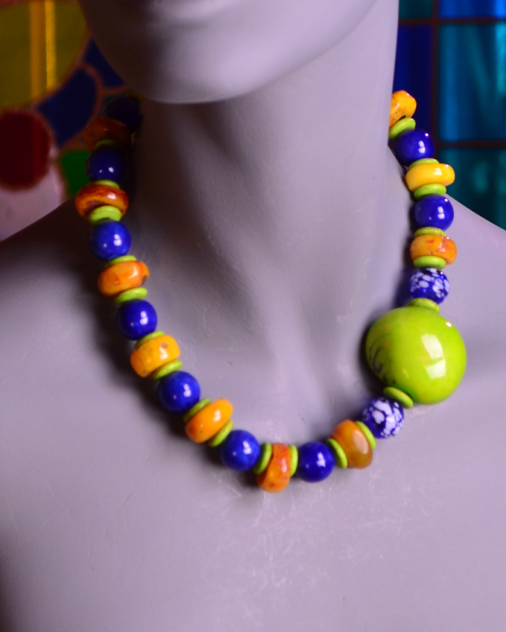 A stunning rare chartreuse Tagua nut, together with navy blue ceramic rounds and natural amber disks, makes this necklace especially exciting. Your friends will kill for it!
