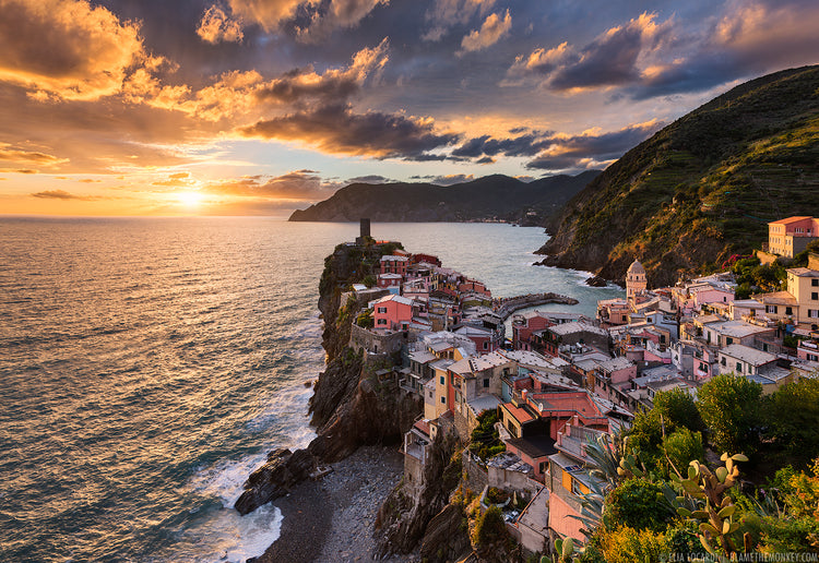 An image from a hill top looking down on a quaint italian mediterranian seaside village. The cloudy sky is lit up near sunset as the vast sea breaks against the shore
