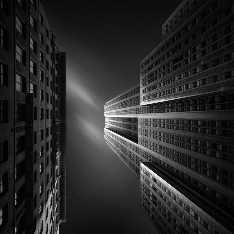 A colorless image looking straight up between two syscraper buildings at the sky, one lit up from the sun, the other in shadow, a faint wisp of a cloud can be seen
