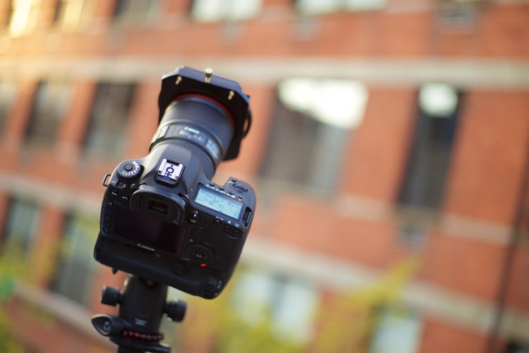An image of a DSLR style camera and lens with a Formatt Hitech filter holder and filter attached to the front. It is mounted to a tripod and pointed at the sky with a brick building in the background
