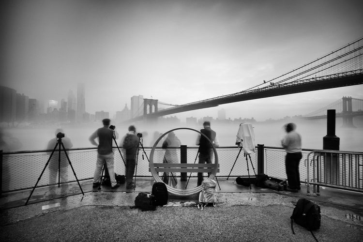An old suspension bridge over a river with heavy fog separating the blurry image of people in the foreground