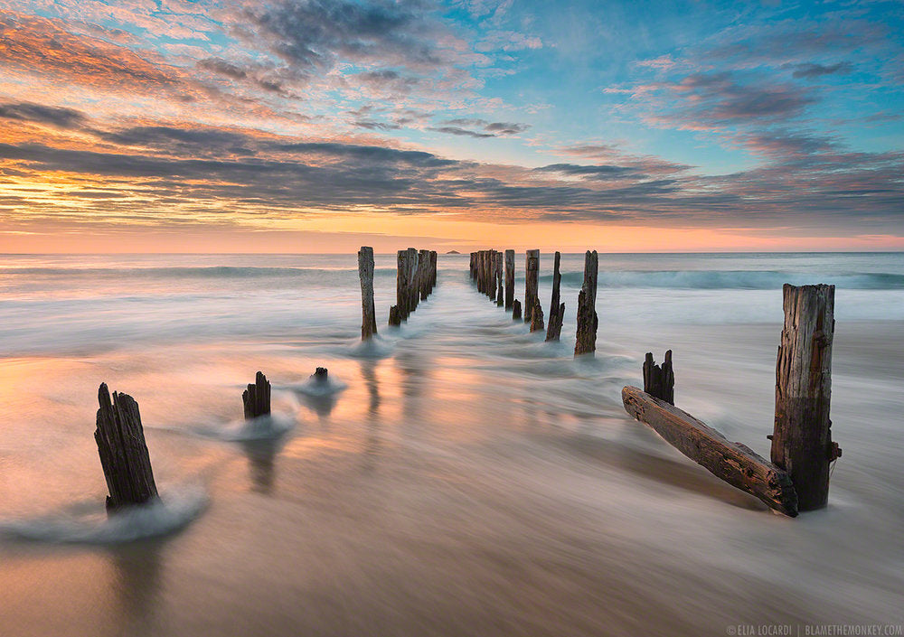 An image at sunset of sea water rushing through the rotted pylons of a collapsed dock