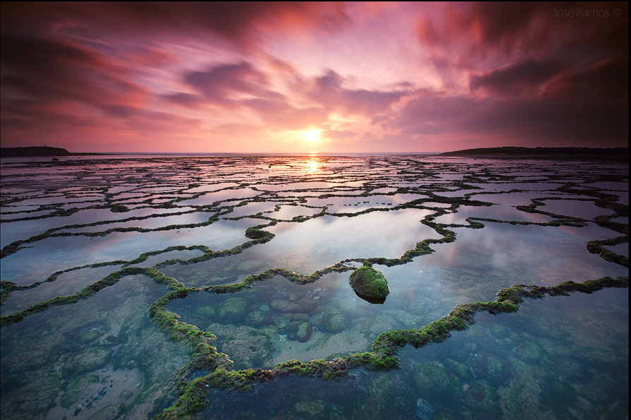 An image shot across a large area of low tide-pools framed by two slivers of land fading off into the ocean at sunset