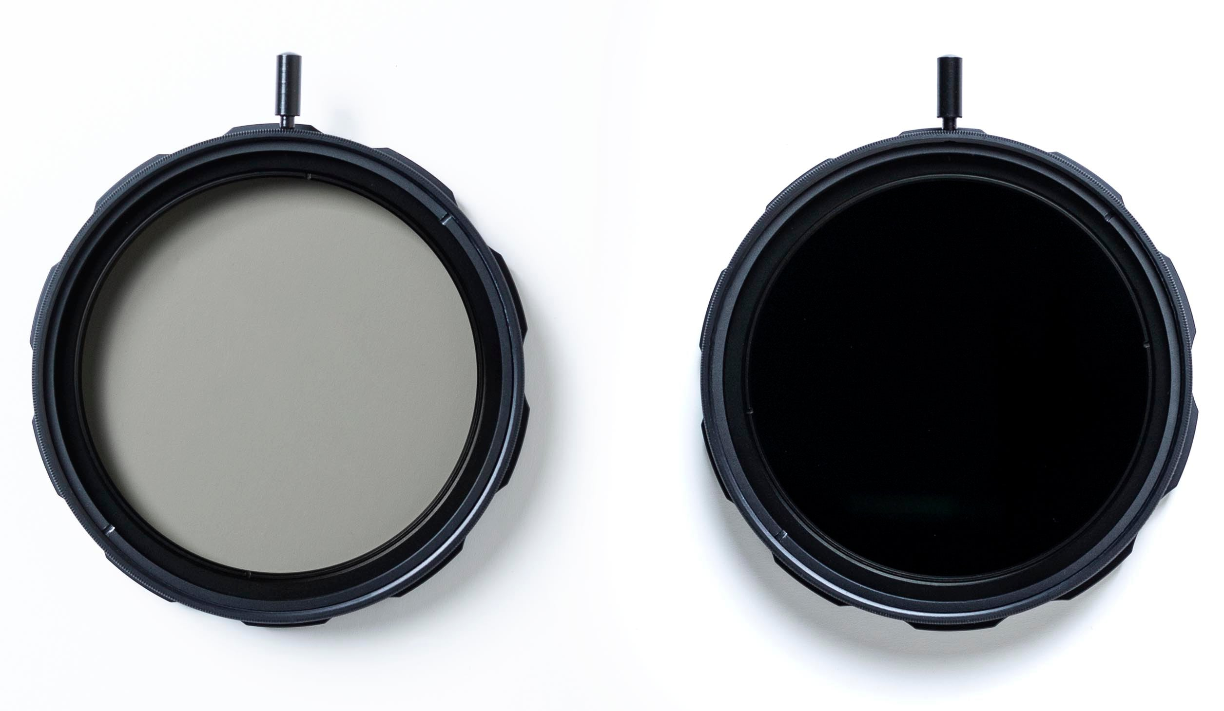 Two Formatt Hitech round threaded Variable ND filters side by side. One is set at minimum light reduction and is see through, the other is set to maximum light reduction and completely opaque to the naked eye
