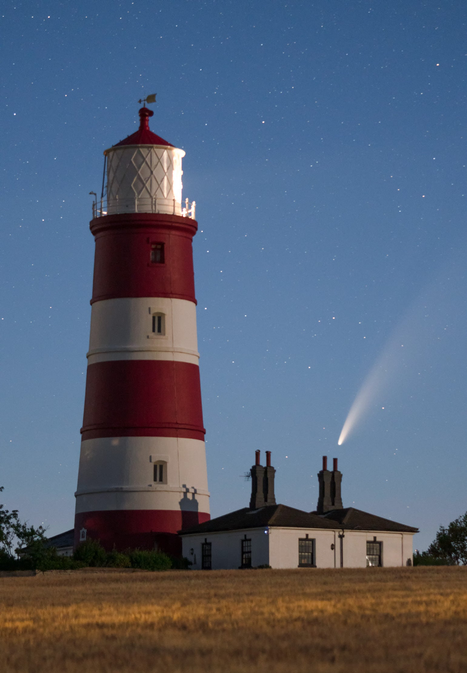 Neowise comet as photographed at night against a Norfolk, UK lighthouse and starlight sky