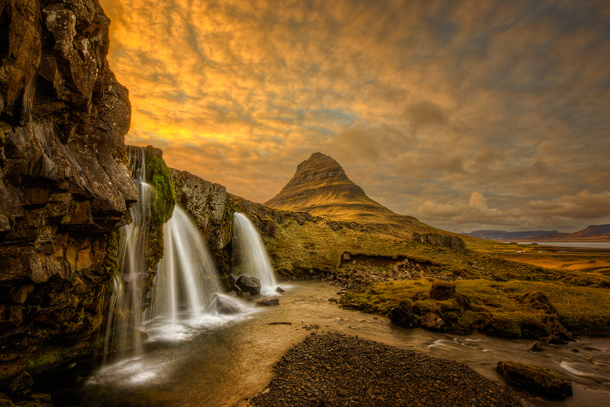 An image of Kirkjufellsfoss in Iceland with a very cloudy sky. There is a steep triangular grass covered mountain in the background with a waterfall in the foreground.