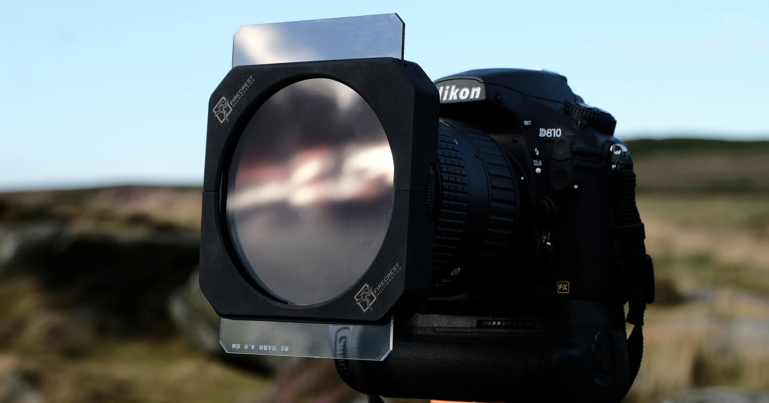 An image showing the Formatt Hitech Firecrest filter holder system and filter on the front of a DSLR style camera and lens