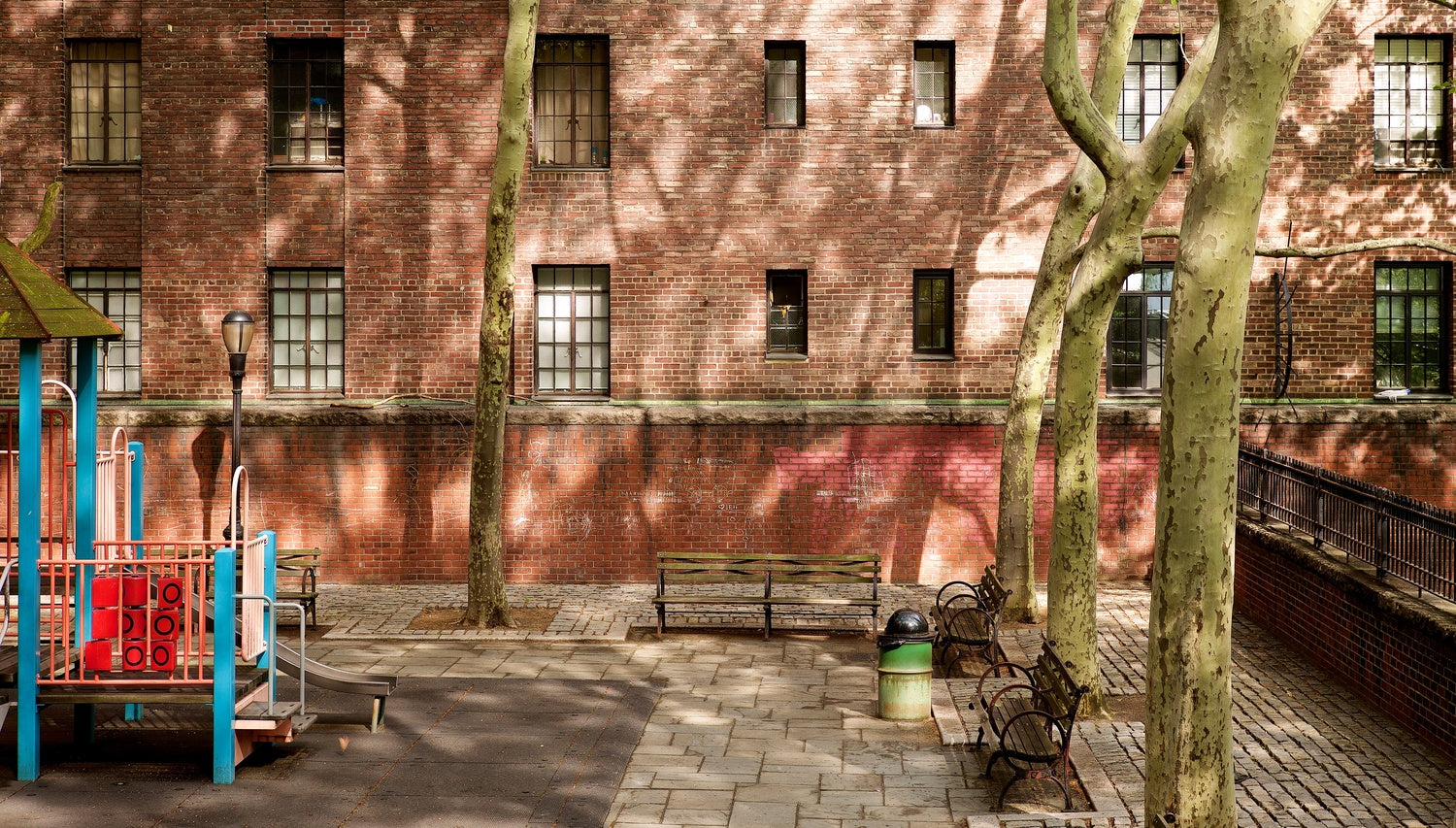 An image of a childrens play park in a city setting with some wooden benches and a brick wall behind a row of trees