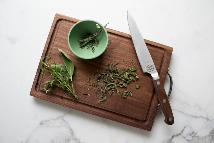 Cutting board with knife and pull and pinch dish with herbs in it.