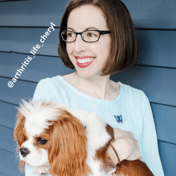 Woman with brown hair and glasses holding light brown and white dog. She is wearing a blue sweater and silver, turquoise and purple butterfly pin for rheumatoid arthritis awareness. The image is tagged as @arthritis_life_cheryl.