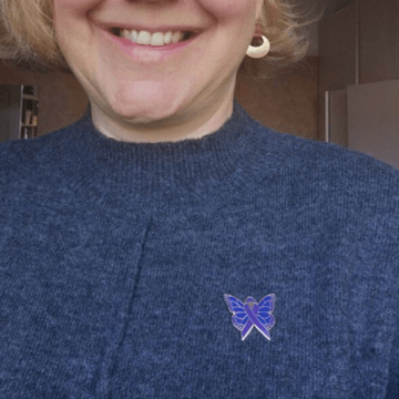 Woman in blue sweater wearing purple and blue butterfly pin for rheumatoid awareness