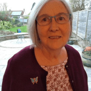 Women with grey hair and glasses wearing turquoise blue and purple silver butterfly pin for rheumatoid awareness on a red sweater