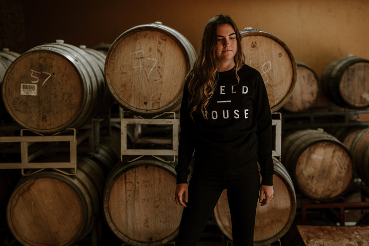 Black unisex crewneck sweater with Field House Brewing logo printed on the front in white. Printed in Abbotsford BC, photo taken in our BRRL ROOM at Field House Farms.