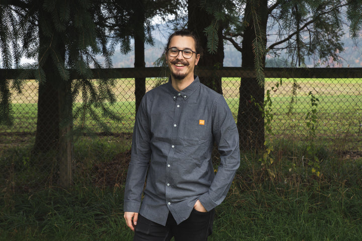 Grey, long sleeve, chambray weave button up featuring an orange Field House Brewing clip label on the pocket