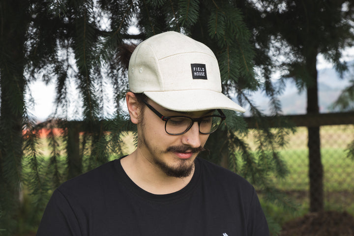 Field House Brewing's natural coloured hemp camp cap with Field House patch on the front. Photo taken at Field House Farms in Abbotsford BC.