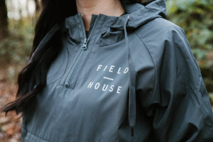 Field House Brewing's grey 1/4 zip windbreaker with Field House printed on the left chest and on the back bottom seam. Photo taken in Abbotsford BC.