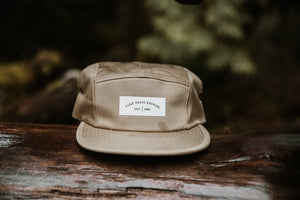 Field House Brewing's beige runners cap with Field House Brewing East Abby white patch on the front and adjustable back closure. Photo take in Abbotsford BC