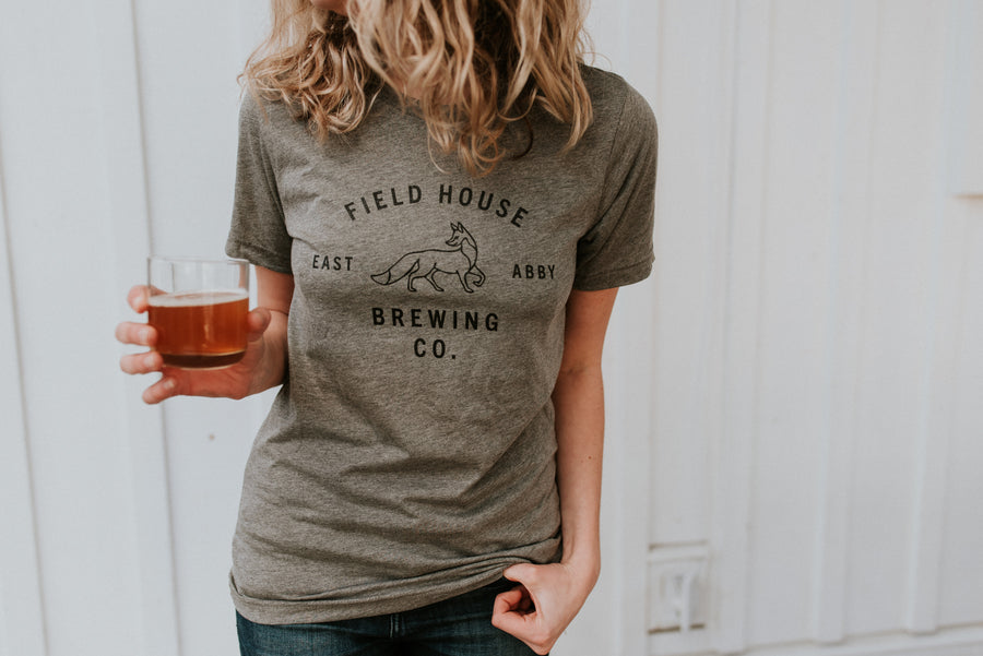 Heather grey, unisex t-shirt with the Field House Brewing logo on the front, printed in black. Photo taken in Abbotsford BC.