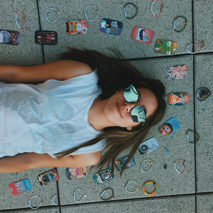 Model wearing Silver Lining Tank... its a white tank with silver wings. She is lying on the ground with tarot cards and bracelets around her.