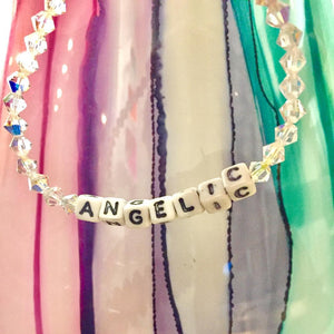 "ANGELIC Sparkle Bracelet. A Swarovski Crystal beaded bracelet with the word ""ANGELIC"" written on it, with white beads and black writing."