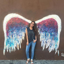 Load image into Gallery viewer, Grey tank with silver and black wings featured on a girl against a colorful mural of angel wings.