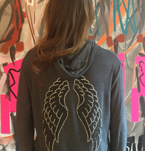 Girl wearing the grey hoodie with silver and black wings on the back. She is standing in front of a colorful wall.