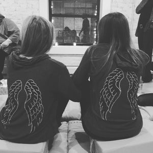 Mother daughter wearing matching grey hoodie with silver and black angel wings on the back.