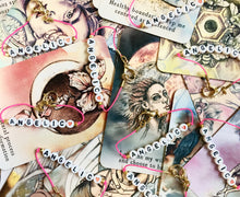 "Load image into Gallery viewer, Photo of our Sweetheart Bracelet, on top of colorful, pretty tarot cards. The bracelet is a pink bracelet with white beads, and black font that says ""ANGELIC"", and has a heart on the end."