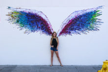 Load image into Gallery viewer, Black tank top with black wings, on the front, featured on a teenager girl standing in front of a mural with colorful angel wings.