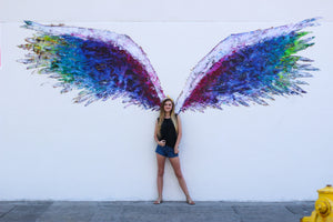 Black tank top with black wings, on the front, featured on a teenager girl standing in front of a mural with colorful angel wings.