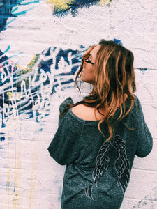Cozy Comfy Crewneck (a grey shirt with black and silver wings on the back), worn on a girl against a white colorful wall.