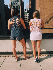 Two girls wearing laser cut angel wing shirts, in pink and grey, with a view of the Empire State Building.