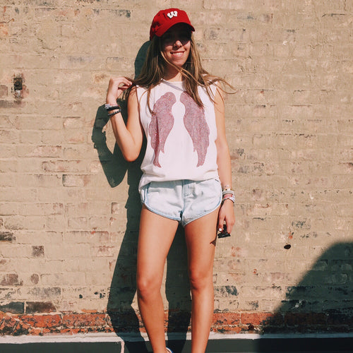 Model wearing a white tank with red wings against a brick wall on a sunny summer day.