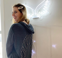 Load image into Gallery viewer, President & founder of the brand wearing the grey hoodie with silver and black wings on the back, standing in front of a white neon angel wing sign.