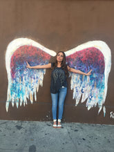 Load image into Gallery viewer, Girl wearing grey tank with silver and black wings against a colorful angel wing wall.