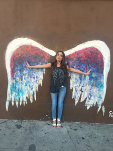 Girl wearing grey tank with silver and black wings against a colorful angel wing wall.