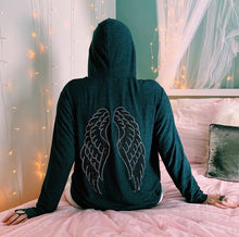 Load image into Gallery viewer, Back of grey hoodie with silver and black angel wings. The model is sitting on a bed with fairy lights around her.