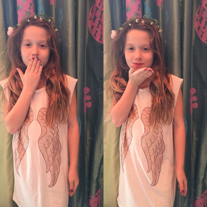 Photo of a little girl wearing a flower crown, and our Heart of Gold Tank. It is a white tank with rose gold wings.