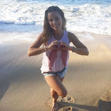 Load image into Gallery viewer, Influencer and wellness-guru Sophie Jaffe, in our Sweetheart Tank (baby pink tank top with red wings on the front), while enjoying a beautiful day on the beaches in Mexico.