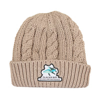 Photo of pink cable knit beanie with patch showing two humpback whales and Glacier Bay National Park and Preserve.