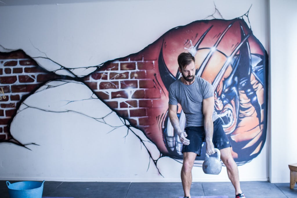 Antoni Stojak holding a kettlebell in 100Strong Manly