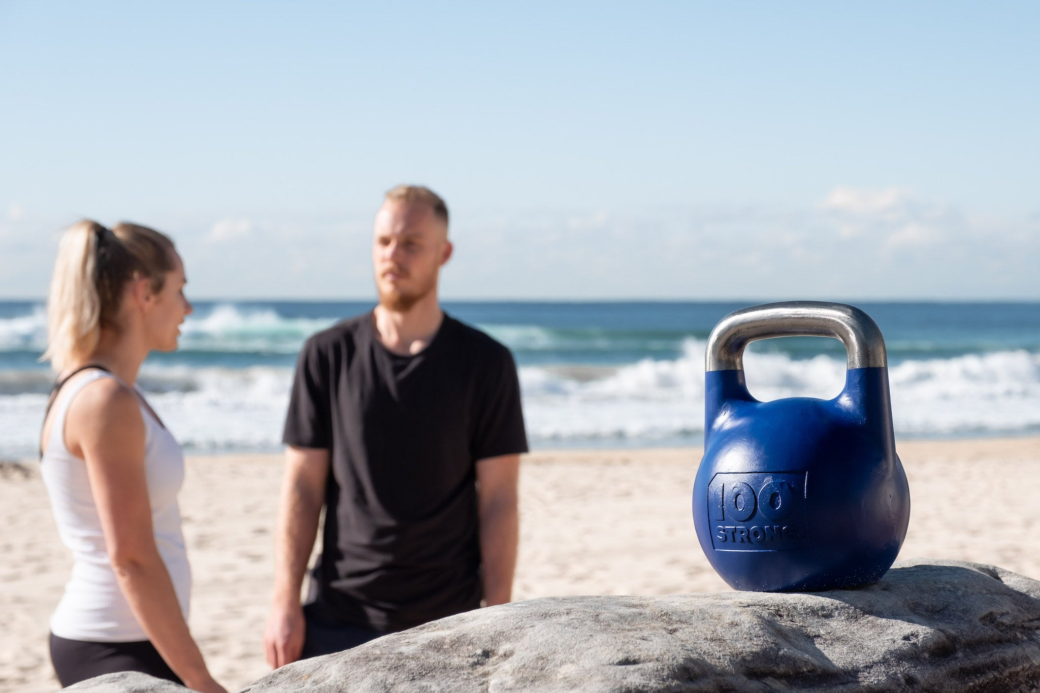 Man and woman talking at Manly Beach with blue 12kg kettlebell in foreground