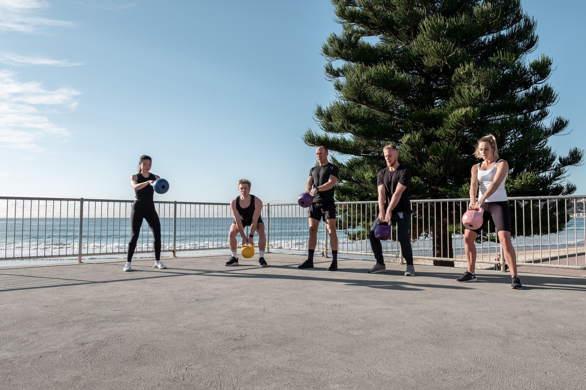 A group of people doing kettlebell training at Manly Beach