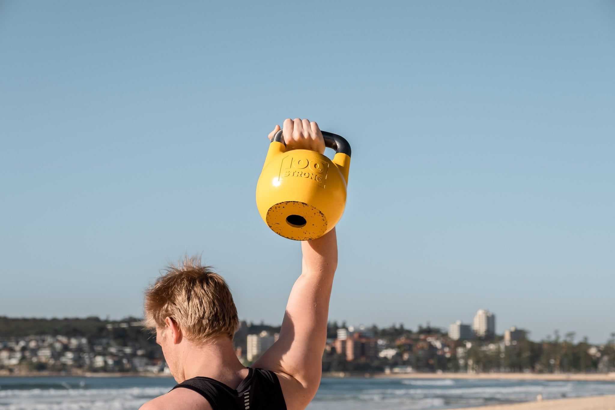 Man holding a 16kg yellow kettlebell overhead at Manly Beach