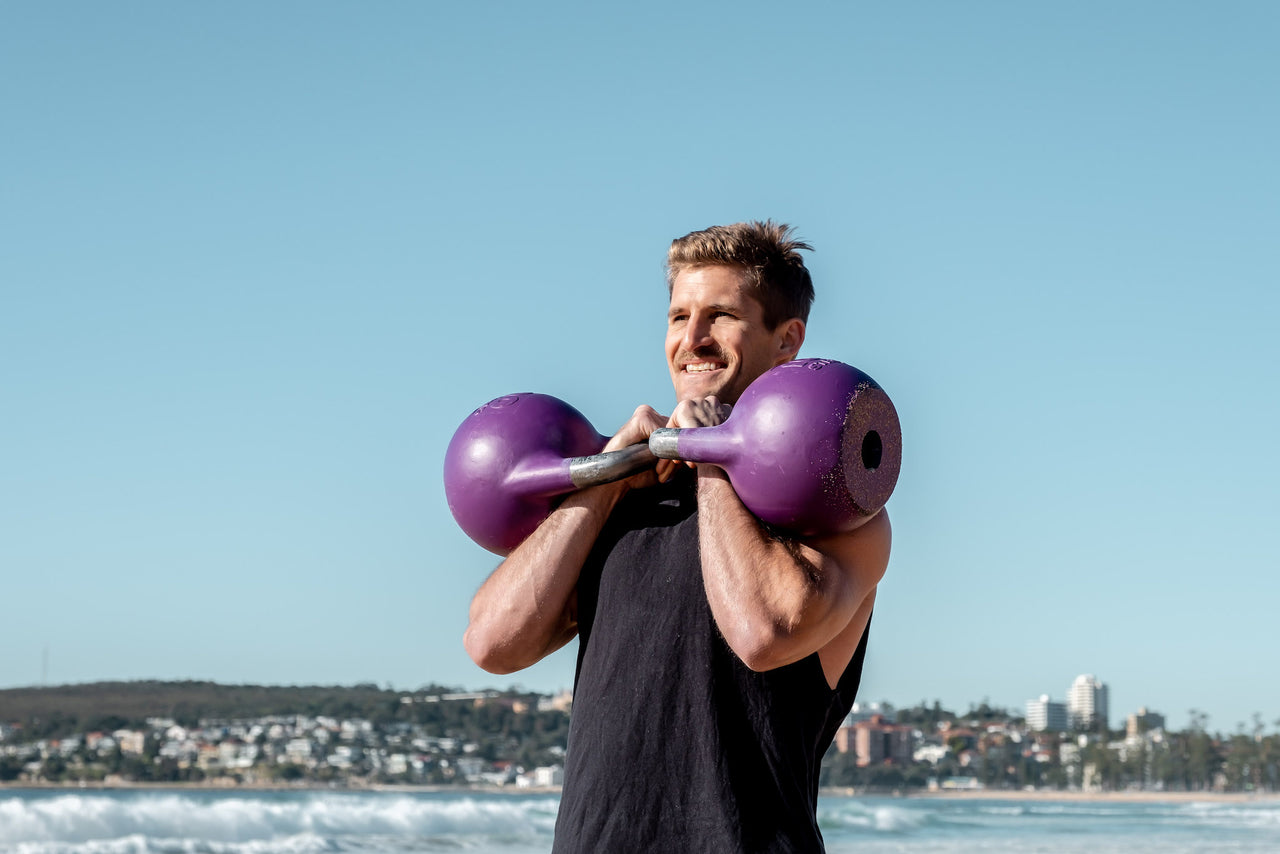 Smiling man holding two purple 18kg kettlebells in rack position at Manly Beach