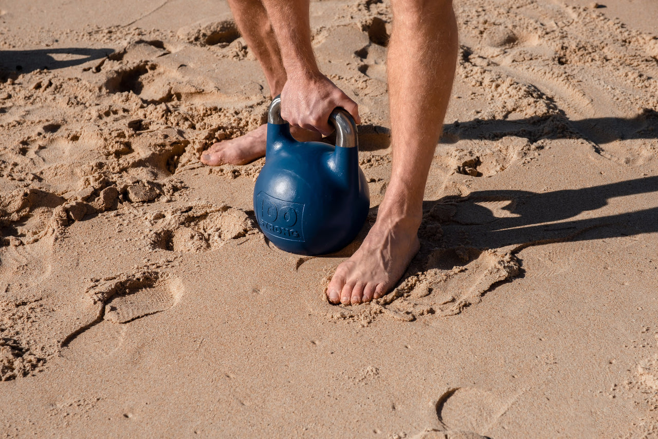 A blue 100Strong 12kg kettlebell being picked up from the sand at Manly Beach