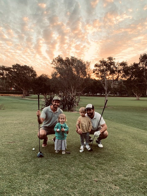 Two men and their children at a golf course