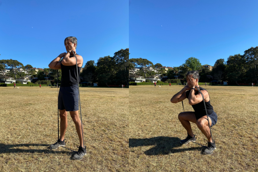 Man doing front squats with resistance band