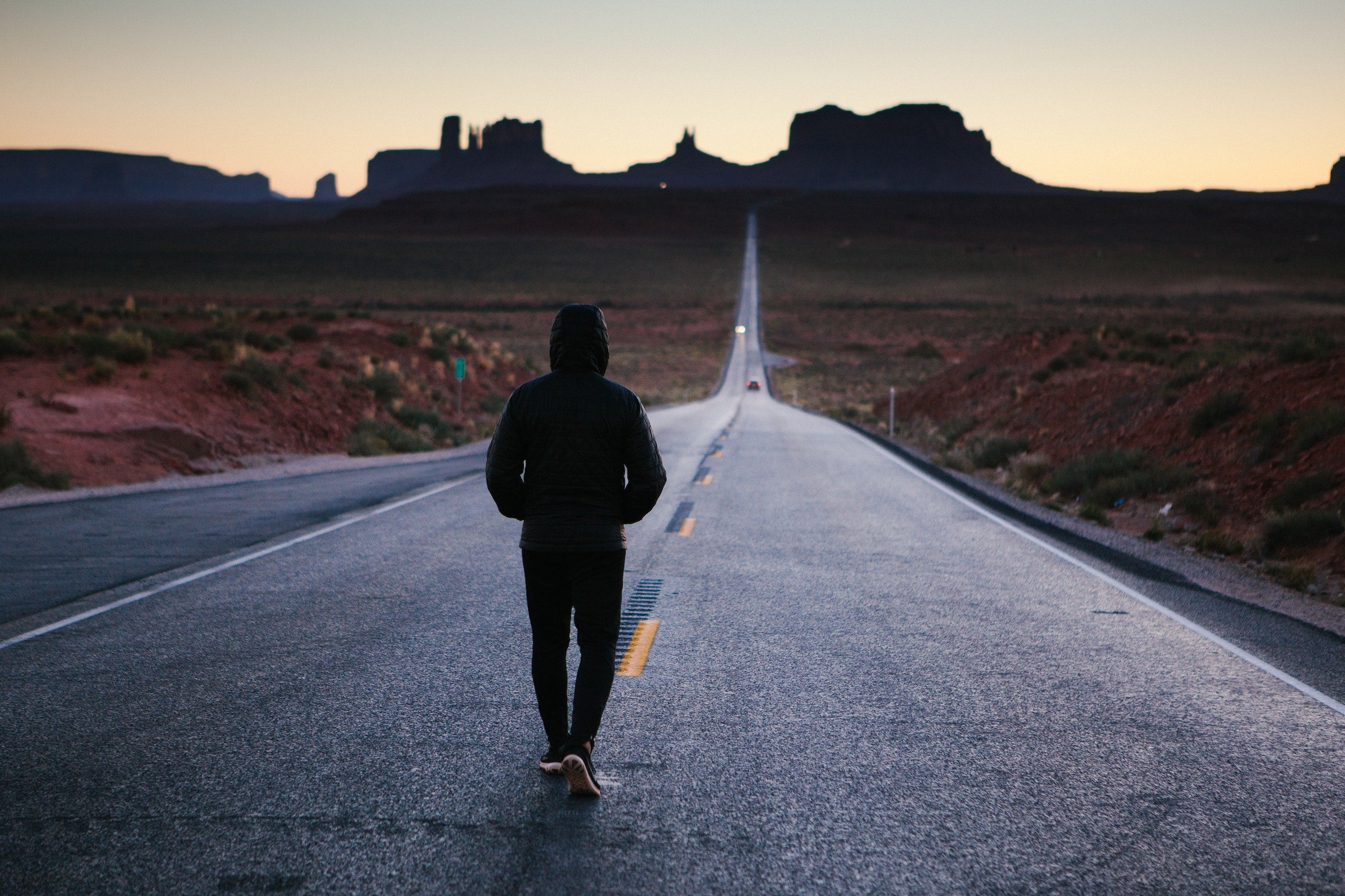 Man walking down a road in Monument Valley